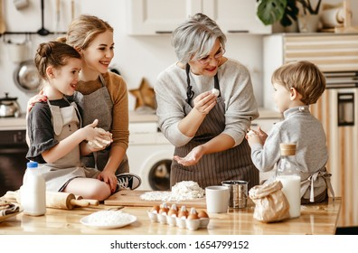 happy family a grandmother with her daughter and grandchildren cooks in kitchen, kneads dough and bakes cookies