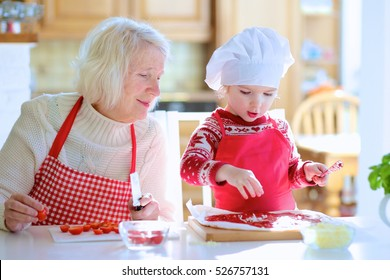 Happy family, grandmother with her granddaughter, preparing delicious pizza together topping it with tomato sauce, vegetables and cheese, sitting at white dining table at bright sunny room at home