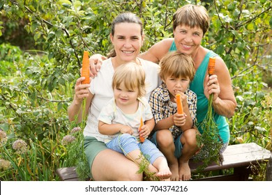 happy family the grandmother, mother and two her children eat vegetables carrot in a garden. Healthy lifestyles concept