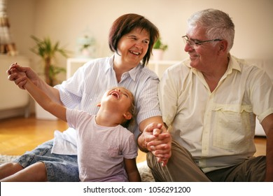 Happy family. Grandparents with granddaughter at home.