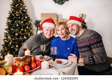Happy family grandparents with grandparents and son in Santa hats sitting at the Christmas table