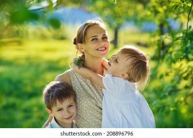 A happy family in the green garden in a sunny spring day: a beautiful young slender mother holding her little laughing daughter in her arms and her smiling son embracing her