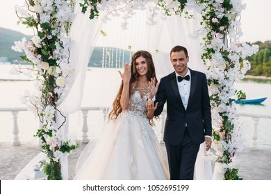 Happy family of groom and bride at wedding day ceremory with arch on background shows their hands with rings. Smiling newlyweds together in wedding suits. Concept of love and happiness