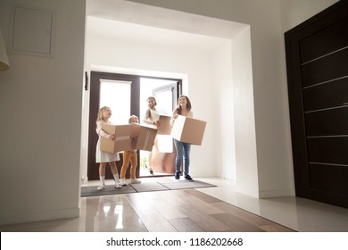 Happy family in hallway. Young excited husband, wife and little children holding cardboard boxes coming first time inside of new house Real estate moving, relocating or loan mortgage, tenant concept