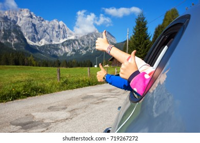 happy family - hands of men and children peering out of the car on a background of mountains.  Dolomites, Italy.