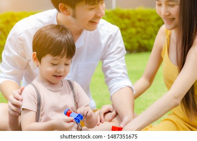 Happy family. Handsome little boy or son playing toy with dad, mother at beautiful park. Cute child get happiness and enjoy life. They laughing together. Cute little boy get lucky, he has warm family