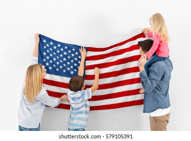 Happy family hanging American flag on wall