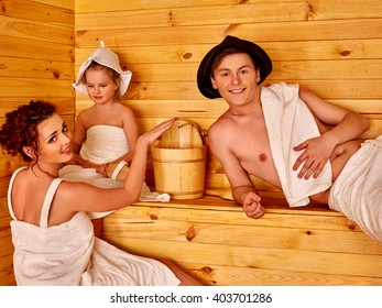 Happy family in hat  relaxing at sauna.
