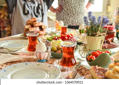 Happy family have breakfast together. Delicious rich Traditional Turkish breakfast include tomatoes, cheese, eggs, bagels, olives and tea cups. Ramadan Suhoor aka Sahur (morning meal before fasting).
