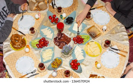Happy family have breakfast together. Delicious rich Traditional Turkish breakfast include cheese, eggs, bagels, olives and tea cups. Ramadan Suhoor aka Sahur (morning meal before fasting).  Top view.