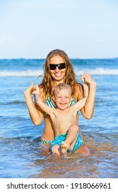 Happy family have fun on tropical sea beach resort. Funny young mother with baby son swim in water pool, raise up the hands. Active lifestyle, people travel activity on summer holiday with kids.