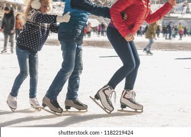 Fröhliche Familie hat eine Outdoor-Aktivität zu Weihnachten, Eislaufen im Freien auf der Piste. Mutter und Kinder haben Winteraktivitäten. Mama, Kinder. Medeo-Stadion. Almaty.