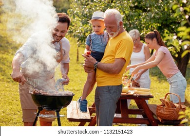 Happy family having barbecue party at summer garden.Leisure,family,holidays and people concept.