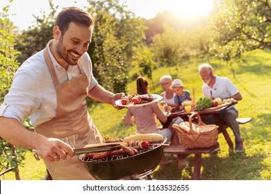 Happy family having barbecue party in backyard.Food,family,fun and happiness concept.