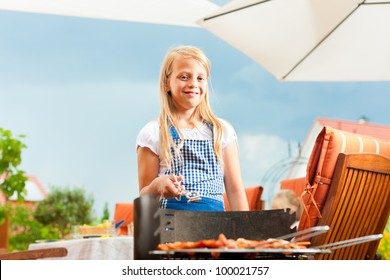 Happy family having a barbecue in summer; the daughter is standing at the grill