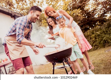 Happy family having a barbecue in their garden in summer.Leisure, food, family and holidays concept.