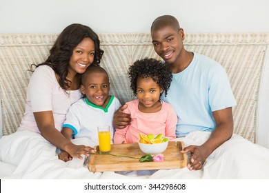 Happy family having breakfast in bed together in the morning