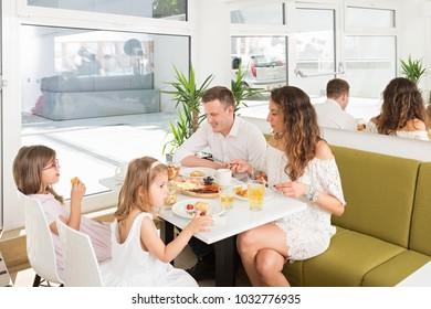Happy family having breakfast in hotel restaurant