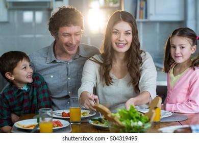 Happy family having breakfast in kitchen