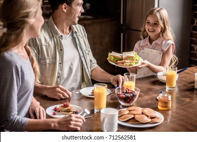 Happy family having breakfast in kitchen. Little girl is bringing sandwiches to her parents and smiling
