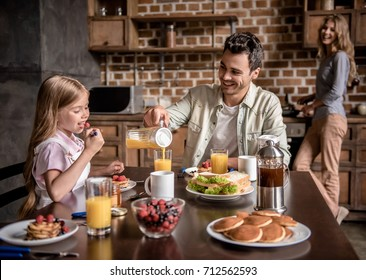 Happy family having breakfast in kitchen. Dad and daughter are sitting at the table while mom is making pancakes
