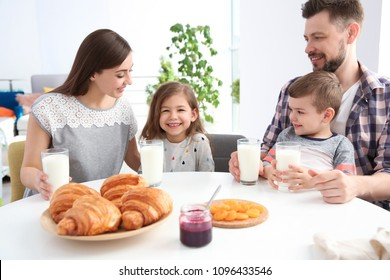 Gia đình hạnh phúc ăn sáng với sữa tại bàn