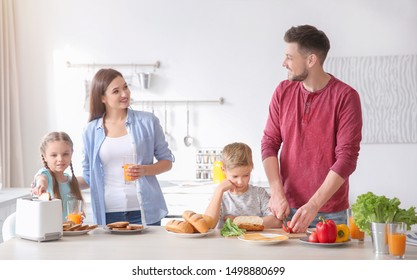 Happy family having breakfast with toasts in kitchen