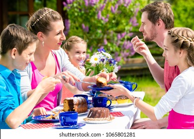 Happy family having coffee time in garden eating cake