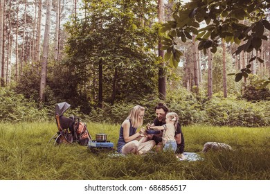Happy family having dinner in woodland.Camping family concept.