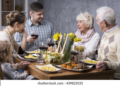 Happy family having elegant dinner together at the table