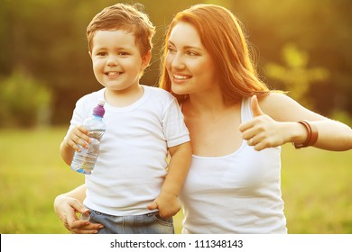happy family having fun. baby boy with brown curly hair and  his mother with ginger hair showing thumbs up. outdoor shot