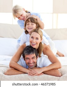 Happy family having fun in the bedroom