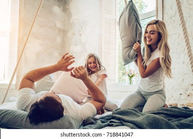 Happy family is having fun in bedroom while pillow battle. Enjoying being together.