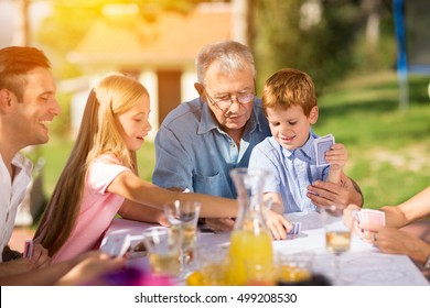 Happy family having fun with cards outdoor