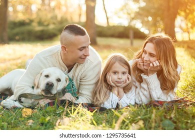 Happy family is having fun with dog labrador are lying on green grass in park.