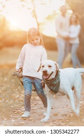 Happy family is having fun with dog labrador outdoors.