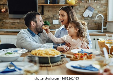 Happy family having fun during lunch at dining table. Little girl is feeding her father.