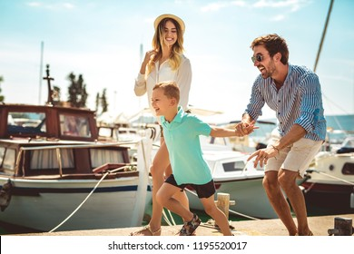 Happy family having fun, enjoying the summer time by the sea.