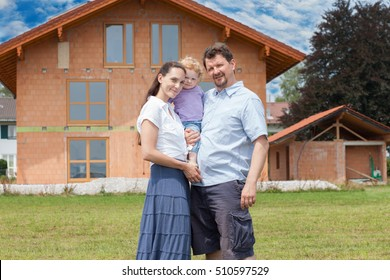 Happy family having fun in front of house