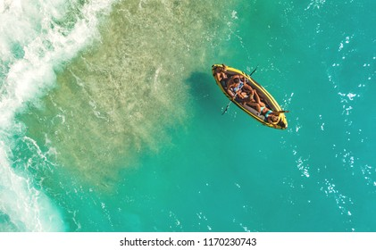 A happy family having fun in a inflatable rubber boat near the sea beach. Beautiful natural background at the summer time from air.