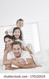 happy family having fun in the morning in parent's bed