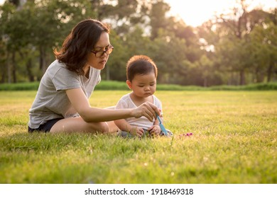 Happy family having fun. Mother playing and having fun with her little baby son on sunshine warm summer day in the city park. Family in park - thailand. Outdoor shot.