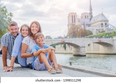 Happy family having fun near Notre-Dame cathedral in Paris, France. Tourists enjoying their vacation in France. Traveling family concept