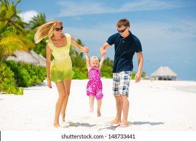 Happy family having fun on the white sandy beach at Maldives