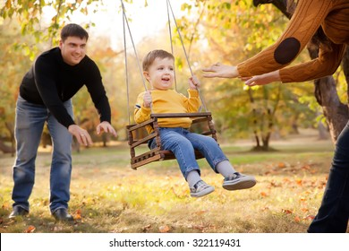 Happy family having fun on a swing ride at a garden a autumn day