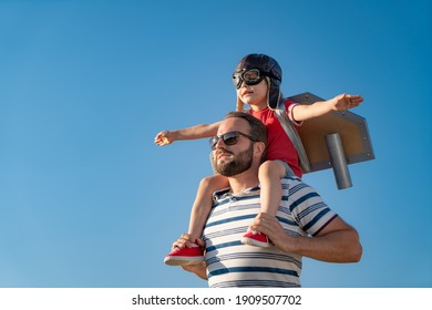 Happy family having fun outdoor. Father and son playing against blue summer sky background. Imagination and freedom concept