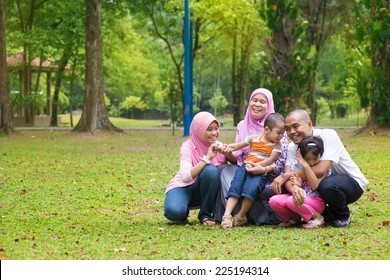 Happy family having fun at outdoor green lawn. Southeast Asian people living lifestyle.