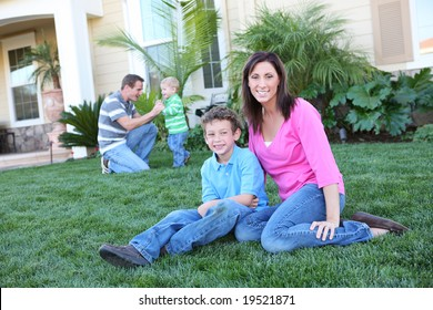 A happy family having fun outdoors in front of their home