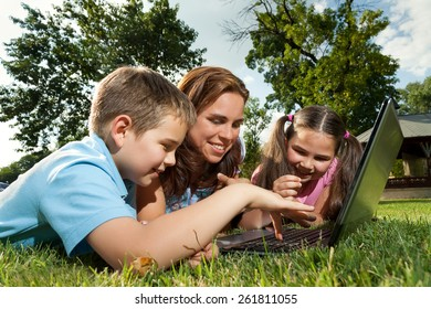Happy family having fun outdoors with a laptop computer