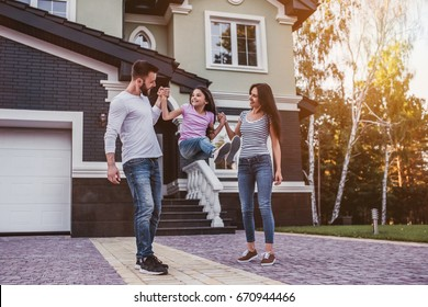 Happy family is having fun outdoors near their private house.